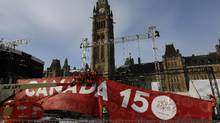 Workers setup a large banner as preparations are made to celebrate Canada's 150th birthday and New Years Eve celebrations to ring in 2017 on Parliament Hill, in Ottawa on Friday, December 30, 2016. (FRED CHARTRAND/THE CANADIAN PRESS)