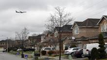 Aircraft approaching Toronto Pearson Airport fly past homes on Driftcurrent Drive in Mississauga on Dec. 16 2015. (Fred Lum/The Globe and Mail)
