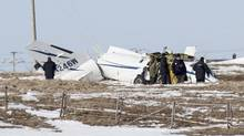National Transportation Safety Board inspectors go over the wrecked airplane in a field Wednesday, March 30, 2016 in Havre-aux-Maison, Quebec where ex-cabinet minister Jean Lapierre, his wife Nicole Beaulieu, two of his brothers and one sister died in a failed landing Tuesday. Quebec's political class remembered Jean Lapierre on Wednesday, one year after the former MP and TV commentator died. (David Noel/THE CANADIAN PRESS)