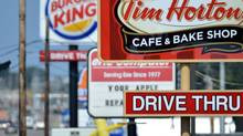 Signs on Peach Street on Tuesday, Aug. 26, 2014, in Erie, Penn. Burger King struck an $11-billion deal to buy Tim Hortons that would create the world's third-largest fast-food company. (Christopher Millette/AP)