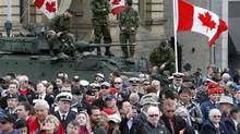 Soldiers stand on military armoured vehicles as people gather on Parliament Hiil in Ottawa during ceremonies for Canada's National Day of Honour Friday May 9, 2014. (FRED CHARTRAND/THE CANADIAN PRESS)