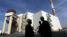 Iranian workers stand in front of the Bushehr nuclear power plant, about 1,200 km south of Tehran in this Oct. 26, 2010 file photo. Iran's judiciary has indicted a member of the country's team that negotiated the nuclear deal with world powers, a spokesman said Sunday, likely an Iranian-Canadian national previously detained by authorities on suspicion of espionage. (STRINGER/REUTERS)