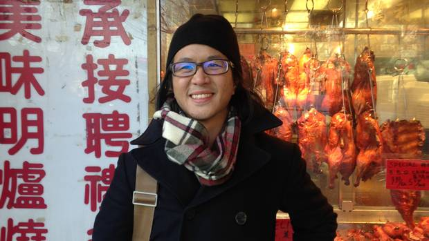 Vancouver housing activist Kevin Huang stands in front of a barbecue shop in Chinatown.