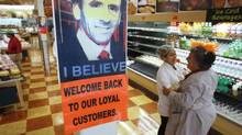 Market Basket employees Cristhian Romero, of Chelsea, Mass., second from right, and Tracie Parker, of Lynn, Mass., right, embrace near a likeness of Arthur T. Demoulas, top, at a Market Basket supermarket location, Thursday, Aug. 28, 2014, in Chelsea. A six-week standoff between thousands of employees of the New England supermarket chain and management has ended with the news that beloved former CEO Demoulas is back in control after buying the entire company. (Steven Senne/AP)