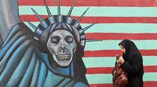 An Iranian woman walks past an anti-U.S. mural painted on the wall of the former American embassy in Tehran on Nov. 19, 2011. (ATTA KENARE/AFP/Getty Images)
