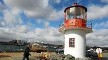 Canadian Coast Guard communications officer Steve Bornais walks past the lighthouse which stands in the parking lot at their base in Dartmouth, N.S., on Oct., 2010. (PAUL DARROW/Paul Darrow for The Globe and Mail)