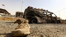 A burnt vehicle belonging to Iraqi security forces is pictured at a checkpoint in east Mosul, one day after radical Sunni Muslim insurgents seized control of the city, June 11, 2014. (STRINGER/IRAQ/REUTERS)