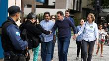 Evangelical bishop Marcelo Crivella ,centre, walks with his wife Sylvia Jane Hodge as he greets voters during the first round of Rio's mayoral elections on Oct. 2. Round 2 of voting is on Sunday. (VANDERLEI ALMEIDA/AFP/Getty Images)