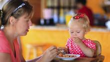 young mother feeding infant daughter in cafe (iStock)
