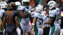 B.C. Lions' Dante Marsh, from left to right, watches as Saskatchewan Roughriders' Xavier Fulton, Weston Dressler and Geroy Simon celebrate Dressler's touchdown during the first half of a CFL game in Vancouver, B.C., on Friday October 4, 2013. (DARRYL DYCK/THE CANADIAN PRESS)