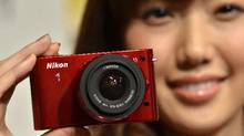 """A model displays a """"Nikon 1 J1"""" interchangeable lens camera in Tokyo on September 21, 2011. Nikon unveiled two models of its new compact camera equipped with a 1-inch sized CMOS image sensor a focusing unit with 73 focus points, and four new lenses. (YOSHIKAZU TSUNO/YOSHIKAZU TSUNO/AFP/Getty Images)"""