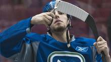 Vancouver Canucks Alex Burrows trims the tape on his stick during practice. REUTERS/Andy Clark (Andy Clark/Reuters)