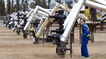 A Statoil oil field worker looks at oil well heads on a well pad at the Statoil oil sands operation near Conklin, Alta., in November. (TODD KOROL/TODD KOROL/REUTERS)