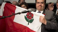Denis Coderre holds a a city flag after winning the Montreal mayoral election. (Ryan Remiorz/THE CANADIAN PRESS)