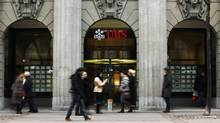 Pedestrians pass a branch of Swiss bank UBS in Zurich, Feb. 5, 2013. The bank paid a $780-million (U.S.) fine in 2009 after admitting it helped several thousand wealthy Americans evade taxes. (MICHAEL BUHOLZER/REUTERS)