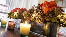 A dining-room centrepiece containing holiday favourites such as amaryllis and pine cones is traditional yet contemporary. Arrangements designed by Bruno Duarte of Fresh Floral Creations.
