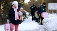 A young girl carries her doll and suitcase as her family, claiming to be from Turkey, illegally cross the U.S.-Canada border into Hemmingford, Que on March 20, 2017. (Christinne Muschi/Reuters)