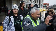 A security guard tries to prevent media from taking photos and recording video as Charles Neil-Curley, left, and Jeremy Roy, back left, arrive in Vancouver, B.C., on Wednesday March 9, 2016. The homeless First Nations men were given one-way bus tickets from North Battleford to Vancouver by the Saskatchewan Ministry of Social Services. (DARRYL DYCK/THE GLOBE AND MAIL)