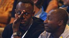 Usain Bolt of Jamaica, left, reacts as he watches the netball match between Jamaica and New Zealand at the 2014 Commonwealth Games in Glasgow, Scotland, July 30, 2014. (RUSSELL CHEYNE/REUTERS)