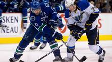 Vancouver Canucks' Ryan Kesler, left, and St. Louis Blues' T.J. Oshie vie for control of the puck during the first period of an NHL hockey game in Vancouver, B.C., on Sunday February 17, 2013. The Blues won 4-3 in a shootout. (Darryl Dyck/The Canadian Press)