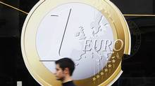A man walks past a pizza shop using a sign of a euro coin to advertise its prices in central Madrid December 9, 2011. (SUSANA VERA/REUTERS)