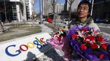 A Chinese Google user carries bouquets of flowers that he wants to present to the Google China headquarters in Beijing (JASON LEE)