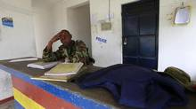 A policeman sits near the scene where his colleague was killed during an attack by gunmen who raided Gamba police station, July 6, 2014. (Joseph Okanga/REUTERS)