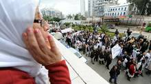 A woman watches from a balcony as Paramedical employees hold a strike in Algiers on Feb. 23, 2011. (FAROUK BATICHE/FAROUK BATICHE/AFP/Getty Images)