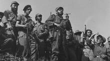 FILE - In this Jan. 7, 1959 file photo, Cuba's rebel leader Fidel Castro, center, and his soldiers make a roadside appearance as they move toward Havana where a welcome is expected the next day. Castro and his fighters ousted dictator Fulgencio Batista and established a communist government. (AP)