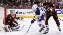 Edmonton Oilers' Connor McDavid tries to get control of the puck as he gets shoved by Arizona Coyotes' Oliver Ekman-Larsson, right, of Sweden, as Coyotes goalie Mike Smith watches during the first period of an NHL hockey game Tuesday, March 22, 2016, in Glendale, Ariz. The Coyotes won 4-2. (Ross D. Franklin/AP)