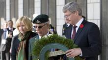 Prime Minister Stephen Harper places a wreath with Canadian Veteran Arsene Dube and Laureen Harper during a Rememberance Day ceremony at the Korean War Memorial in Seoul, Korea Thursday Nov.11, 2010. (Adrian Wyld/The Canadian Press/Adrian Wyld/The Canadian Press)