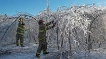 Members of the Baie Sainte Anne Fire Department clear a road in Escuminac, N.B.., on (Diane Doiron/THE CANADIAN PRESS)