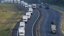 A Russian convoy of trucks carrying humanitarian aid for Ukraine travels along a road south of the city of Voronezh. (MAXIM SHEMETOV/REUTERS)