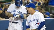 Toronto Blue Jays hitting coach Kevin Seitzer (right) talks to player Brett Lawrie before he hits in Toronto, April 9, 2014. (Fred Thornhill/THE CANADIAN PRESS)