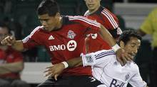 Vancouver Whitecaps' Camilo Sanvezzo, right, fights for the ball with Toronto FC's Junior Burgos, left, as Eric Avila looks on during the first half of a soccer match at the Walt Disney World Pro Soccer Classic Finals, Saturday, March 3, 2012, in Lake Buena Vista, Fla. (AP Photo/Reinhold Matay) (Reinhold Matay/AP)