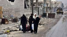 Syrian residents fleeing the eastern part of Aleppo walk through a street in Masaken Hanano, a former rebel-held district which was retaken by the regime forces last week, on Nov. 30, 2016. (GEORGE OURFALIAN/AFP/Getty Images)