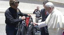 Pope Francis is presented with a leather Harley Davidson jacket during the weekly audience in Saint Peter's Square at the Vatican June 12, 2013. (OSSERVATORE ROMANO/REUTERS)