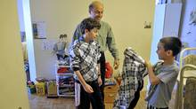 Rony Sehayek, an IT specialist who's been out of work for a year and his sons, Dan, left, and Matthew pose get dressed for photos in their Brampton apartment, October 20, 2010. Sehayek can no longer afford to put his boys through karate lessons. (J.P. Moczulski/The Globe and Mail)