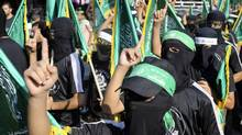Masked Hamas members take part in a rally in support of the armed Palestinian factions in Rafah in the southern Gaza Strip on Aug. 17, 2014. (IBRAHEEM ABU MUSTAFA/REUTERS)