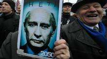 """Opposition activists take part in their authorized rally at the Bolotnaya Square in central Moscow, on December 10, 2011, to protest against the alleging mass fraud in the December 4 parliamentary polls. The poster depicts Russia's Prime Minister Vladimir Putin looking old and reads: """"2050 - No!"""" Tens of thousands of election protesters turned out today in Moscow and other major cities across Russia in open defiance to strongman Vladimir Putin's 12-year rule. (YURI KADOBNOV/AFP/Getty Images/YURI KADOBNOV/AFP/Getty Images)"""