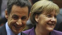 French President Nicolas Sarkozy, left, speaks with German Chancellor Angela Merkel during a round table session at an EU summit in Brussels on Friday, Dec. 9, 2011. (Geert Vanden Wijngaert/AP)