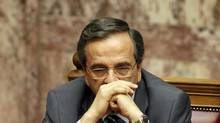 Greek Prime Minister Antonis Samaras listens as Leader of Greeces' Radical left party ( SYRIZA) Alexis Tsipras speaks at the Parliament in Athens Saturday, July 7 2012. (KOSTAS TSIRONIS/AP)