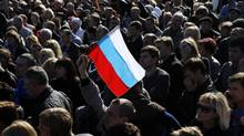 A pro-Russian activist holds a Russian flag during a rally in Donetsk's Lenin Square in Ukraine on March 23, 2014. (YANNIS BEHRAKIS/REUTERS)