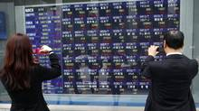 Passersby take pictures of a screen displaying stock prices in Tokyo. (ISSEI KATO/Issei Kato/Reuters)