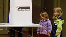 Children wait as their mother marks her ballot for the federal election at a Victoria polling station on May 2, 2011. (DARRYL DYCK/THE CANADIAN PRESS)