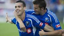 Montreal Impact's Felipe Martins, left, celebrates with teammate Jeb Brovsky after scoring against the Seattle Sounders' during first half MLS soccer action in Montreal, Saturday, June 16, 2012. (Graham Hughes/THE CANADIAN PRESS)
