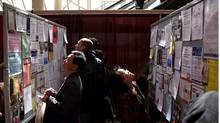 Job seekers look at the ads on display at the National Job Fair and Training Expo in Toronto. (Fernando Morales/The Globe and Mail)