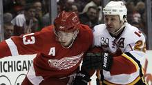 Detroit Red Wings center Pavel Datsyuk, left, of Russia, and Calgary Flames center Daymond Langkow battle for the puck in the first period of a NHL hockey game in Detroit, Tuesday, March 9, 2010. (AP Photo/Paul Sancya) (Paul Sancya)