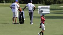 A youngster carries a sign displaying scores past Tiger Woods as he waits to hit on the 16th fairway (Patrick Semansky/AP)