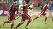 Toronto FC 's Andrew Wiedeman (centre) celebrates scoring against New England Revolution as Toronto's Jonathan Osorio (left) looks on during first half MLS action in Toronto on Friday August 30, 2013. (Chris Young/THE CANADIAN PRESS)